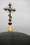 一个金黄十字架坐在教会圆顶顶部 免版税图库摄影