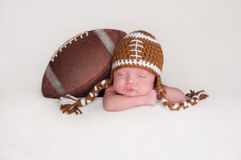 戴一个钩针编织的橄榄球帽子的新出生的男婴 免版税库存照片
