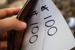 一个钱包在他的手上和在它上与题字的一张纸 免版税库存图片