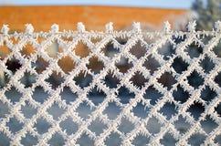 一个铁丝网的特写镜头视图有霜的与冰晶在蓝天下有被弄脏的背景 图库摄影