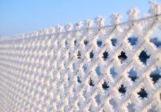 一个铁丝网的特写镜头视图有霜的与冰晶在蓝天下有被弄脏的背景 免版税库存照片