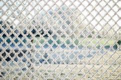 一个铁丝网的特写镜头视图有霜的与冰晶在蓝天下有被弄脏的背景 库存照片