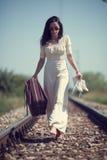 一个铁路减速火箭的样式的妇女带着手提箱 免版税库存照片