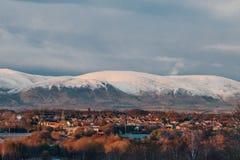 一个镇在苏格兰由在多雪的montain背景的日落光点燃了  免版税库存照片