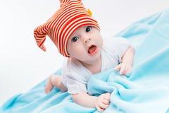 一个镶边帽子的小孩在一条蓝色毯子 图库摄影