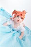 一个镶边帽子的小孩在一条蓝色毯子 免版税库存图片