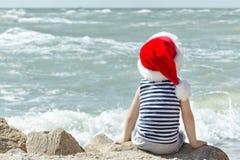 一个镶边T恤杉和圣诞老人帽子的男孩坐海滨 回到视图 库存照片