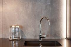 一个长方形设计师厨房水槽的细节与镀铬物水龙头的对灰色织地不很细墙壁 库存照片