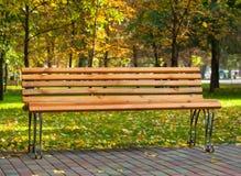 一个长木凳在公园,反对黄色下落的叶子背景  库存照片