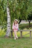 一个长木凳的愉快的女孩在桦树附近 免版税图库摄影