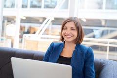 一个长沙发的微笑的女实业家在有膝上型计算机的办公室 免版税图库摄影