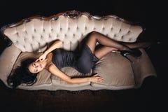 一个长沙发的性感的女孩在黑礼服 图库摄影