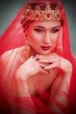 一个长的红色礼服和皇家冠的美丽的女孩 免版税库存照片