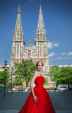 一个长的红色礼服和皇家冠的美丽的女孩 免版税库存图片