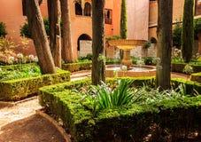 一个闪耀的喷泉的一个美好的夏日视图在阿尔罕布拉宫摩尔人宫殿,格拉纳达,西班牙庭院里  免版税库存图片
