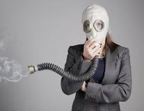 一个防毒面具的妇女有香烟的 免版税库存照片