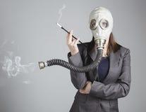 一个防毒面具的妇女有香烟的 库存图片