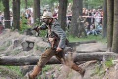 一个防毒面具的战士在与一杆枪的攻势在他的手上 免版税图库摄影