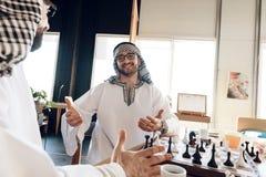 一个阿拉伯商人封死另一使用的棋在桌上在旅馆客房 库存照片