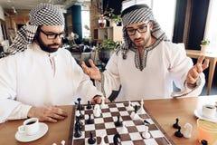一个阿拉伯商人封死另一使用的棋在桌上在旅馆客房 免版税图库摄影