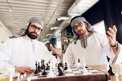 一个阿拉伯商人封死另一使用的棋在桌上在旅馆客房 免版税库存照片