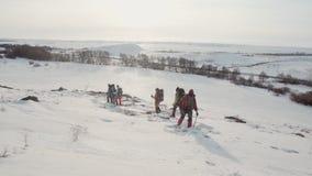 一个陡峭的雪倾斜在下降在小组登山人下,在滑雪杆帮助下,他们轻轻地把足迹留在 股票视频