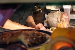 一个院长在一家地方餐馆在佛罗伦萨准备意大利盘 看法是一个潜随猎物者或者一名潜在的顾客 免版税库存照片