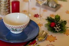 一个陶瓷碗的细节在圣诞节桌上的与陶器、蜡烛和装饰在桌布 免版税库存照片