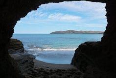 一个隧道的出口在岩石的在海岸 免版税库存图片