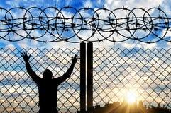 一个难民的剪影在篱芭附近的 免版税库存照片