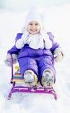 一个雪撬的可爱的小女孩冬天晴天 免版税库存照片