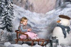 一个雪撬的女孩在雪人旁边 免版税库存图片