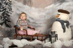 一个雪撬的女孩在雪人旁边 图库摄影