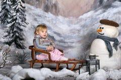 一个雪撬的女孩在雪人旁边 库存图片