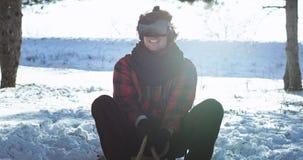 一个雪橇的愉快的吸引人卷发人使用打虚拟现实的玻璃一场真正比赛,当享用时 股票视频