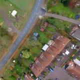 一个露台的房子的鸟瞰图有庭院和草坪的在没有汽车的一条乡下公路旁边 库存照片