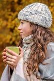 一个青少年女孩的画象一个温暖的帽子和围巾大块举行的咖啡杯的茶 免版税库存照片