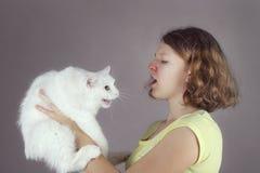 一个青少年过敏女孩拿着一只安哥拉猫猫 免版税库存照片