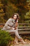 一个非常俏丽,微笑的女孩的画象编织毛线衣的,与 图库摄影