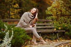 一个非常俏丽,微笑的女孩的画象编织毛线衣的,与 库存图片