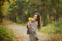 一个非常俏丽,微笑的女孩的画象编织毛线衣的,与 库存照片