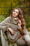 一个非常俏丽,微笑的女孩的画象编织毛线衣的,与 免版税库存图片