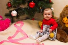 一个非常小女孩坐在与五颜六色的装饰的一棵圣诞树下 圣诞节新的结构树年 免版税库存照片