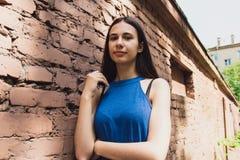 一个非常美丽和快乐的女孩在街道上站立在砖墙附近 免版税图库摄影