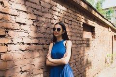 一个非常美丽和快乐的女孩在街道上站立在砖墙附近 库存图片