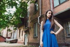 一个非常美丽和快乐的女孩在街道上站立在砖墙附近 免版税库存图片