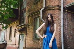 一个非常美丽和快乐的女孩在街道上站立在砖墙附近 免版税库存照片