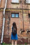 一个非常美丽和快乐的女孩在街道上站立在砖墙附近 库存照片