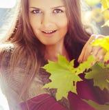 一个非常美丽的女孩的画象有槭树的在秋天离开, 库存照片