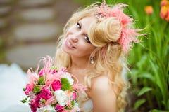 一个非常美丽的新娘金发碧眼的女人的画象一件白色礼服的与 免版税库存图片